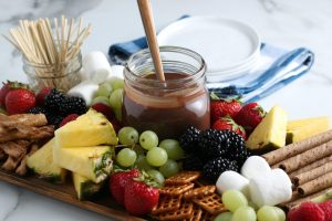 chocolate sauce and assorted dipping items on a wooden tray