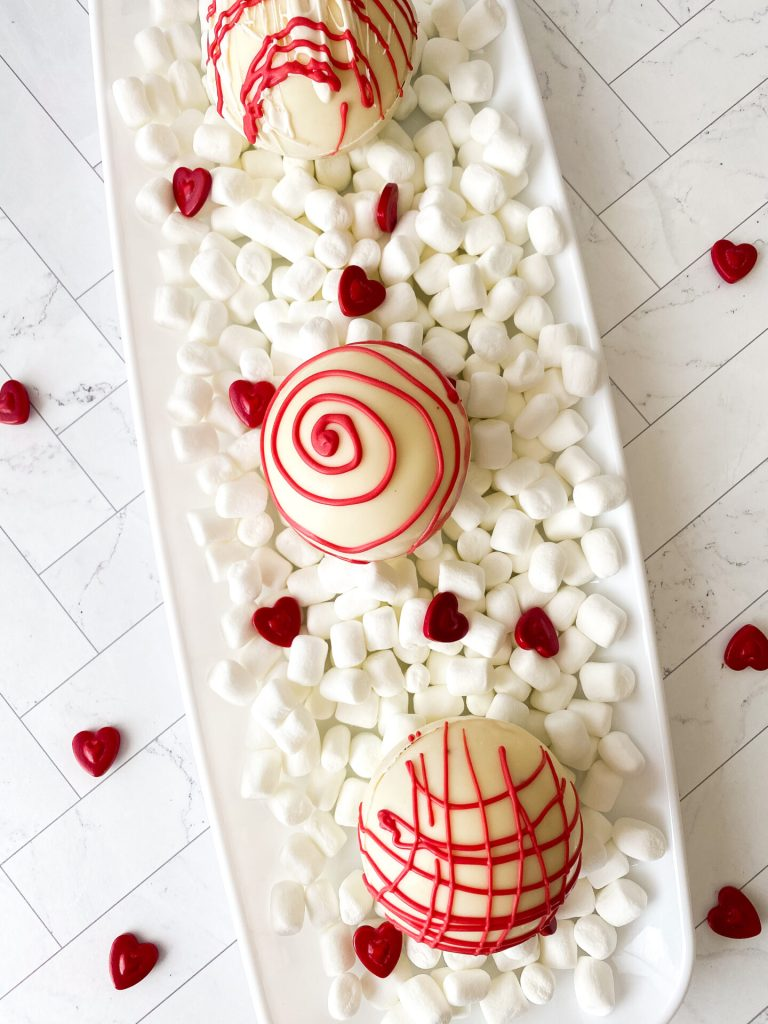 overhead shot of white chocolate hot chocolate bombs on a white tray