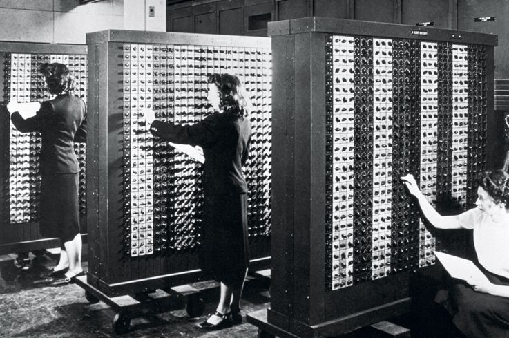 ca. 1940s, USA --- Computer operators program ENIAC, the first electronic digital computer, by adjusting rows of switches. --- Image by © CORBIS