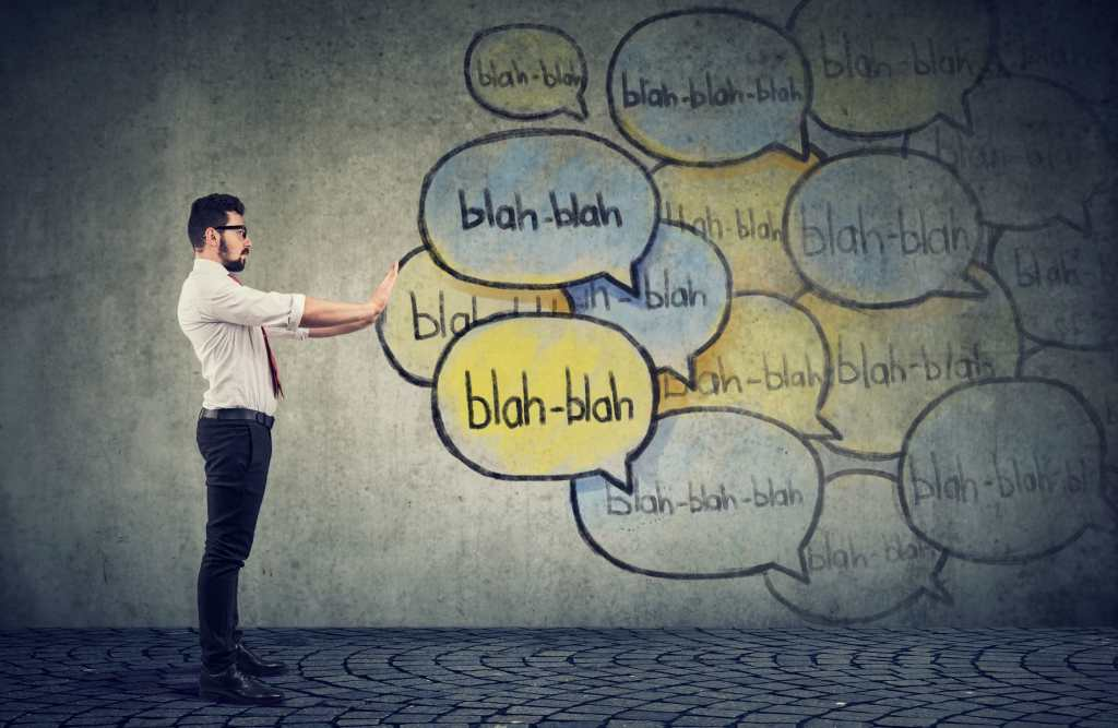 Man standing by a wall which features a group of speech bubbles in yellow and blue, with black writing that says blah blah blah blah - the man is pushing the speech bubbles away. He is wearing smart work clothing.