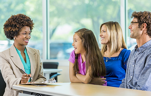 Happy family meeting with African American Teacher