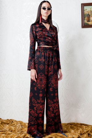 Red and black flame printed silk trousers. Worn with matching Joy silk wrap blouse. Paired together to make a strong empowering entrance not to be forgotten.