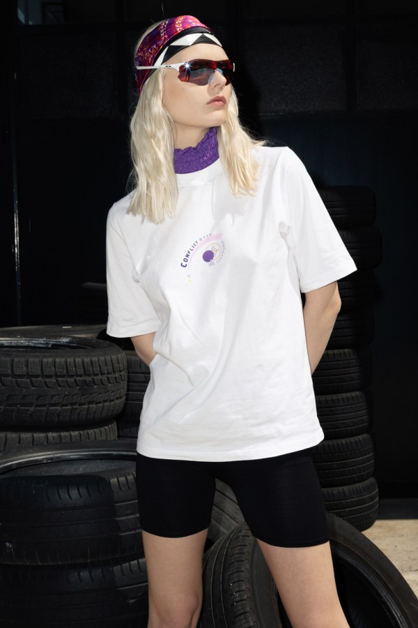 White cotton tee with purple frill neck detail. Printed with the new Conflict of Ego In Motion Logo. Worn with layered skinny silk headbands also from the new In Motion collection.
