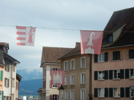 Jura flag and Delémont flag at the front. Not sure what the church-looking one is.