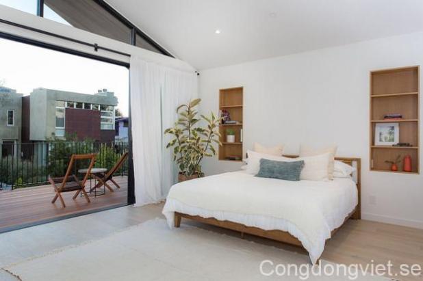 Phòng ngủ được trang trí theo phong cách Scandinavian với ban công ốp gỗ mát mẻ và đẹp mắt.