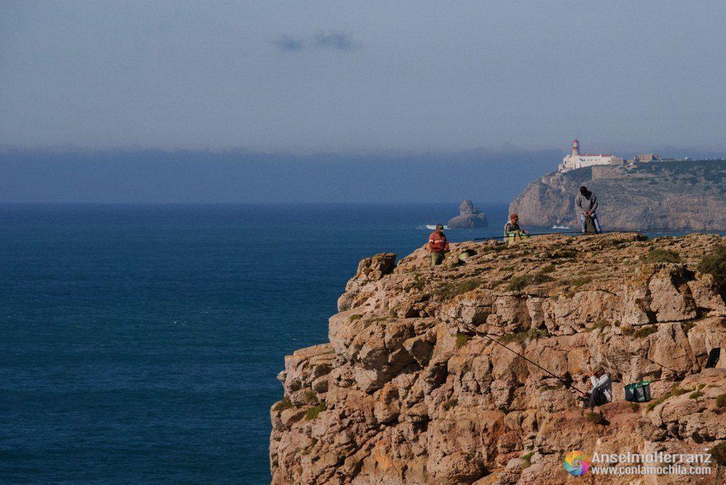 Pescadores de la fortaleza de Sagres en sus puestos de pesca. - Se ve a los pescadores sentados en el acantilado y al fondo el faro del Cabo de San Vicente