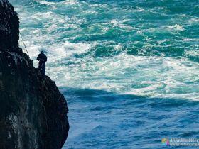 Pescador de la fortaleza de Sagres en uno de los salientes del acantilado. Mas o menos a media pared entre el nivel del mar y la parte superior del acantilado, un pescador se prepara para lazar la caña.
