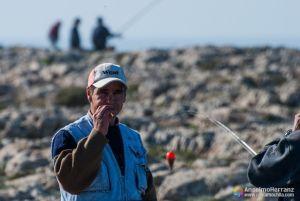 Pescador de la Fortaleza de Sagres fumando - Portugal - Alguno de los pescadores descansan y fuman un cigarro. El de la foto, con gorra blanca y chaleco, mira fijamente a la cámara sujetando con la mano el cigarrillo que tiene en la boca