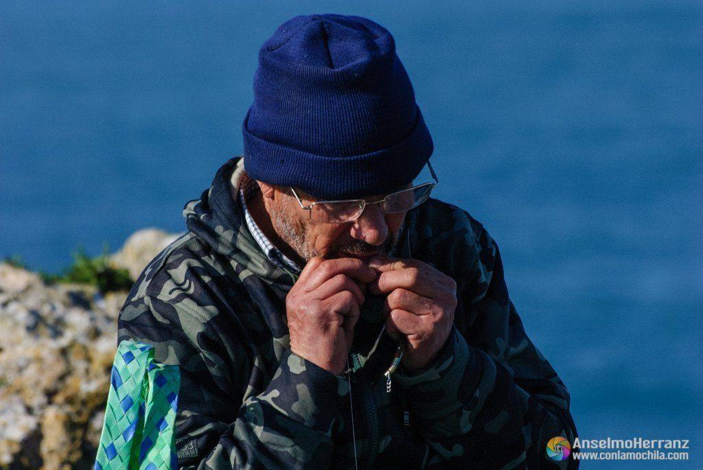 Pescador de la Fortaleza de Sagres - Portugal - Un pescador se ayuda de los dientes para terminar el nudo del anzuelo.