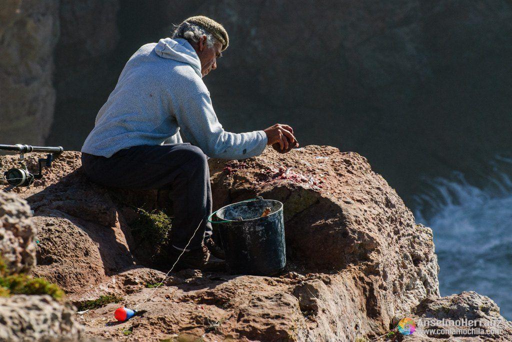 Pescador preparando cebo en la fortaleza de Sagres - Portugal - Un pescador sentado sobre las rocas, saca de un cubo pequeños peces que machaca con una piedra para preparar el cebo que pondrá en sus anzuelos.