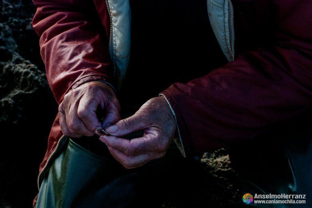 Preparando los anzuelos para comenzar la pesca. Las manos de un pescador curtidas por los años y el mar preparan el anzuelo.