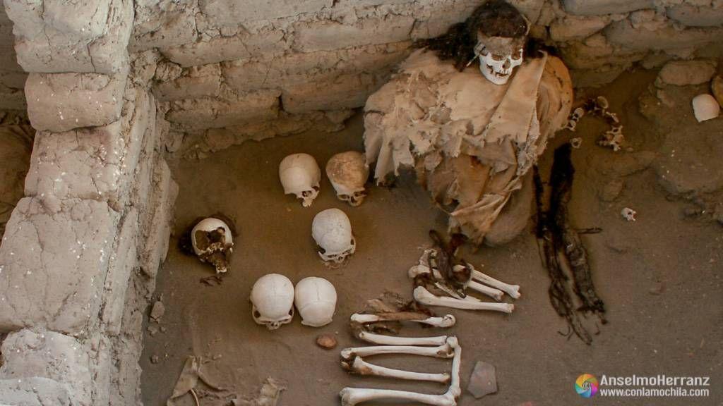Momia rodeada de cráneos y otros huesos en el cementerio de Chauchilla - Perú