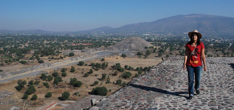 Raquel en lo alto de la pirámide del templo del Sol con la pirámide del templo de la luna al fondo - Teotihuacán - México