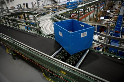 The system is designed to transport totes of outdoor goods from the pick-to-pick routing area to one of two packaging lines.