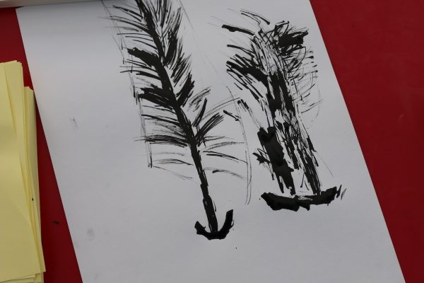 A child's ink drawing of a pine tree on a red Formica table