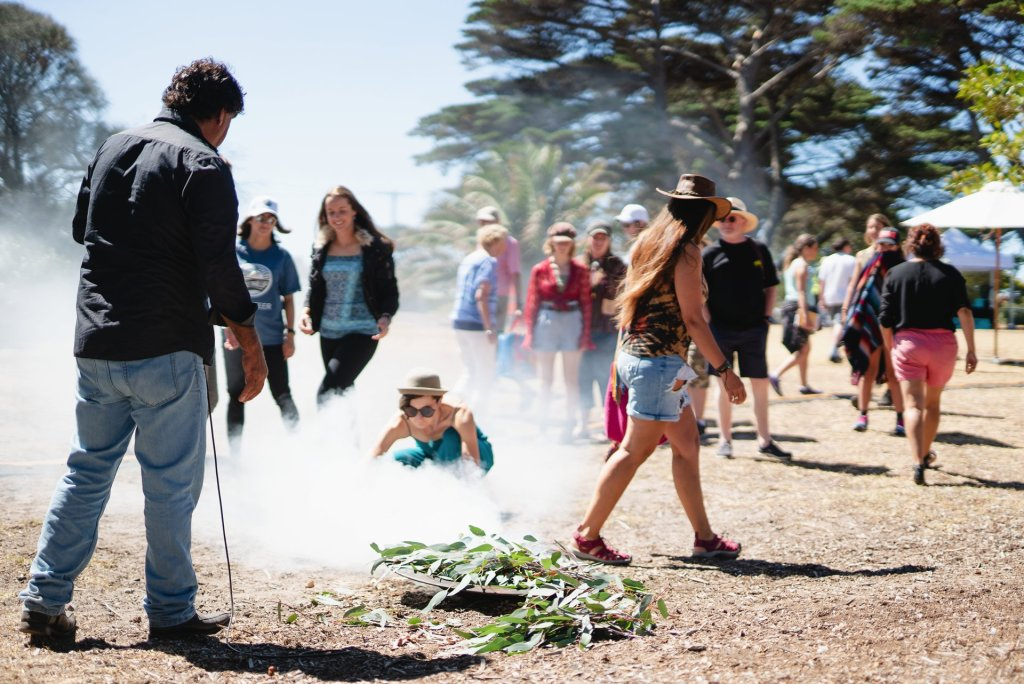 Uncle Shane from the Bunurong Land Council invites festivalgoers to walk through the smoke during Welcome to Country. Image: Tim Brown