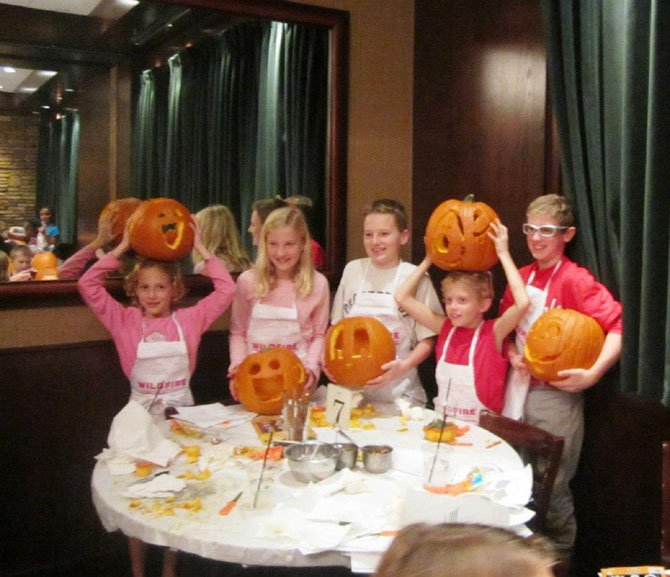 Local children show off their masterpieces after a pumpkin carving class at Wildfire Tysons Galleria. Proceeds from the class go to Food for Others, a Northern Virginia food bank.