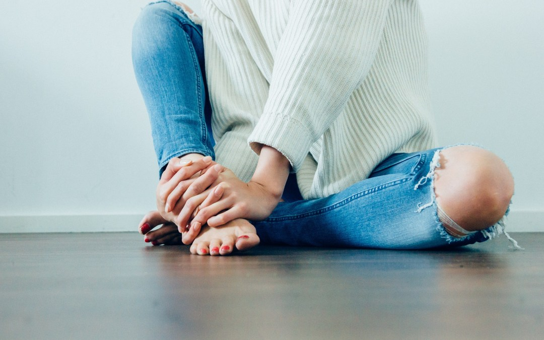 Woman sitting on the floorwith her hands wrapped around her foot
