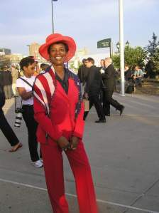 Black woman wearing a red suit and an American flag scarf