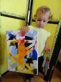 My granddaughter Edie showing the artwork she made in the Lindleys' toddler class.