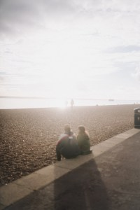 a couple sitting on the edge of the beach with the sun behind them, shot with the 1/4 tiffen promist