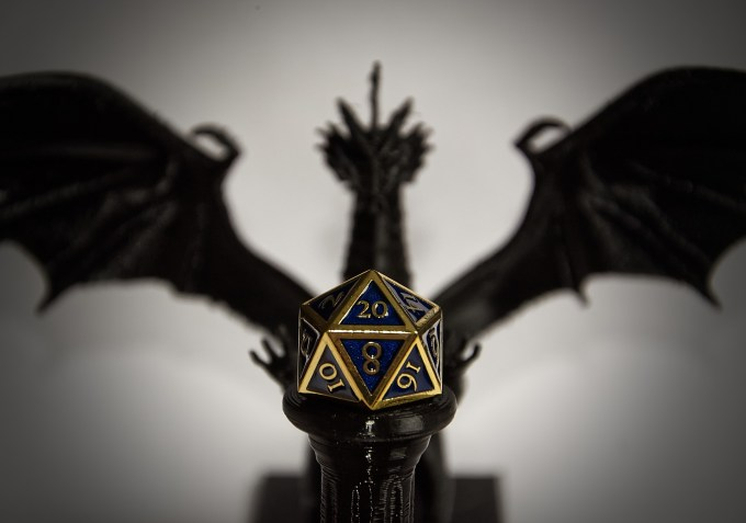 a dragon in the background behind a black pillar with a metallic looking D20 in blue and gold