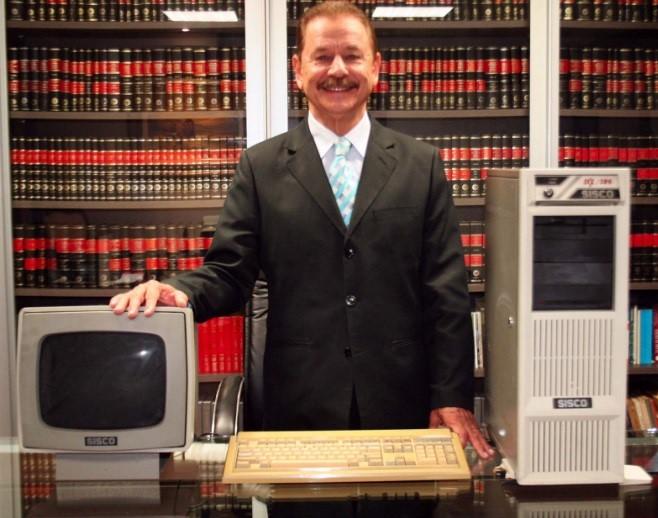Um homem ao lado de um PC.