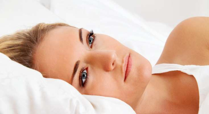 A woman trying to sleep, but unable