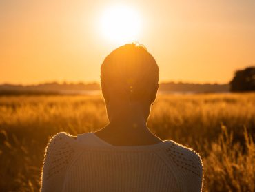 Woman in field staring into the sun | calm stress using the elements for self-care | Conscious Content cropped