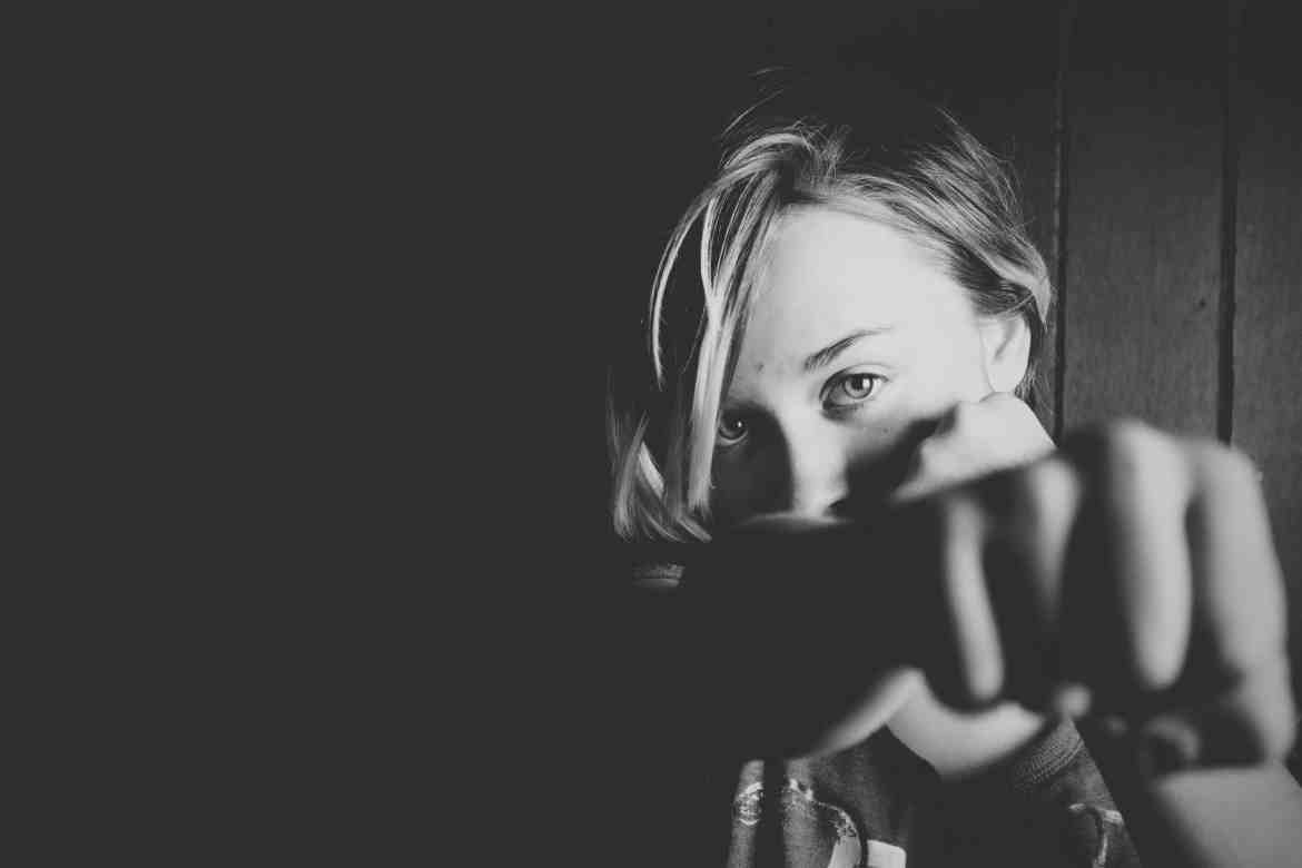 Woman punching towards camera with fist in front of her mouth black and white | Fighting words won't help us heal in a pandemic | Conscious Content