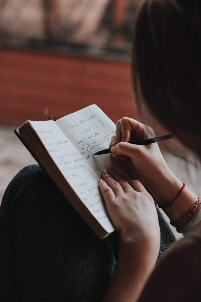 Woman journaling | Conscious Content