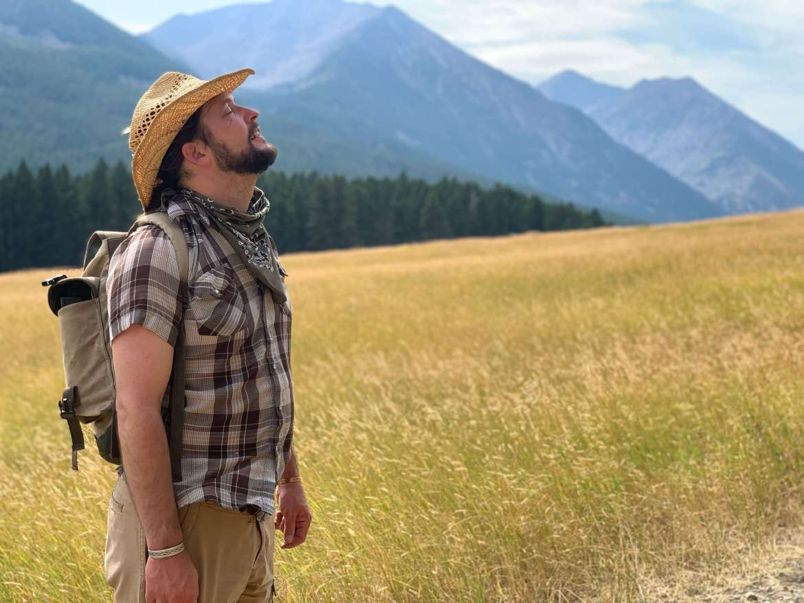 Man in the mountains breathing in fresh air | Connect with yourself to honor the earth | Earth day | Conscious Content