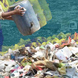 landfill in india. man dumping waste.