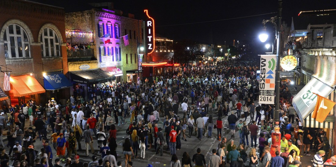 People Walk Along Sixth Street on the Last Day of South by Southwest in Austin Texas 15 March 2014