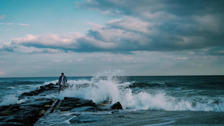producer nurko stands in crashing ocean waves