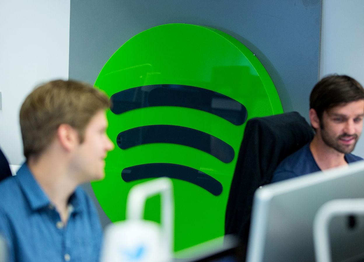 Spotify employees work at computers against company logo