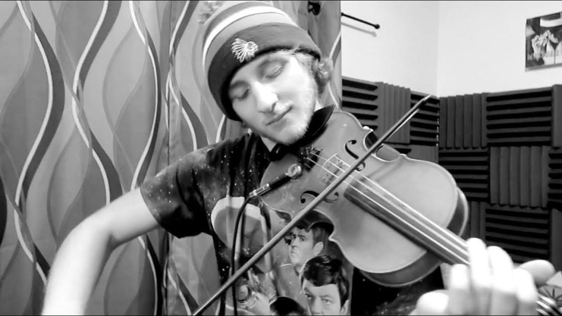 Taiga Collective Founder Josh Teed plays violin in a music studio