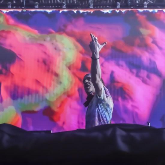 Liquid Stranger throws hands up during LAN set colorful background