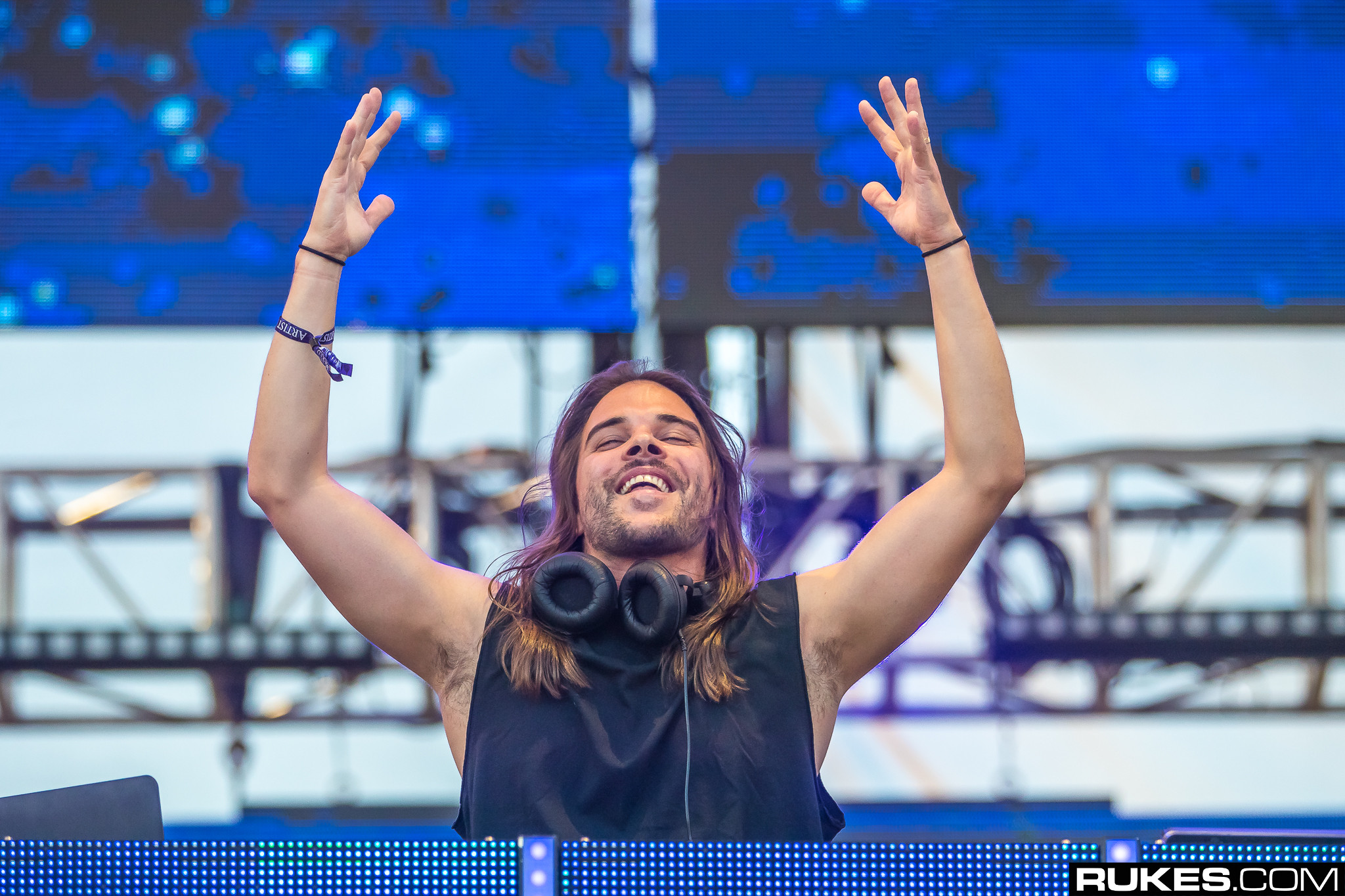 Seven Lions DJs and throws hands up during set LED blue background