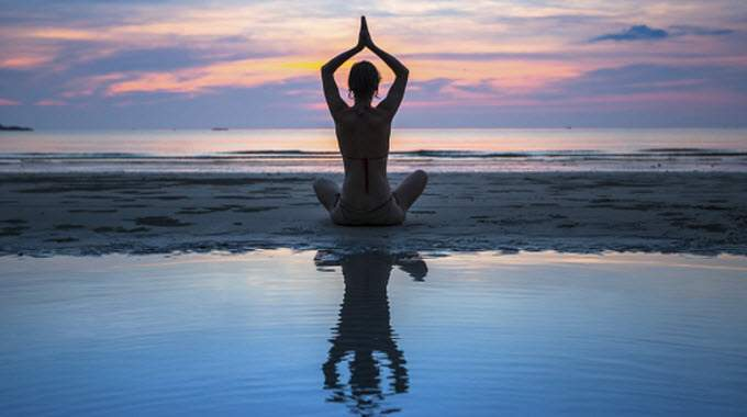 woman meditating-on-beach