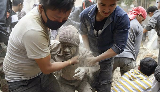 NEPAL-EARTHQUAKE-aftermath-man-helped-by-two-others