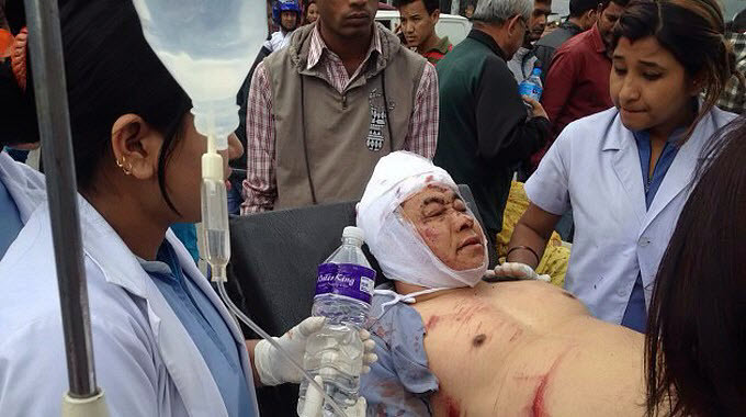 nepal-earthquake-man-on-stretcher-cared-for-by-others