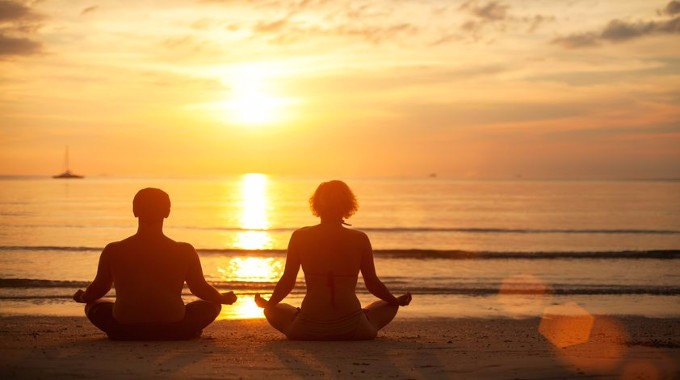 Couple meditating on the beach-compressed
