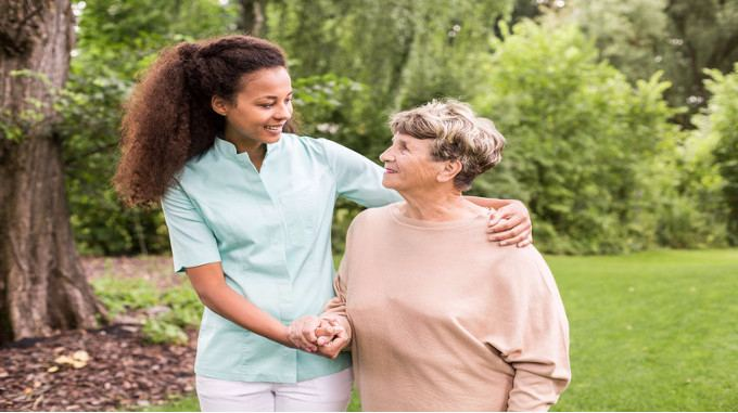 nurse-is-walking-around-with-elder-lady-compressed