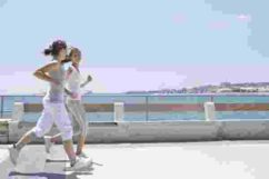 ttwo girls running by the sea