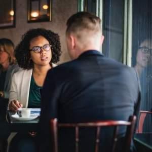 emploi storytelling _ homme de dos et femme au cours d'un entretien au café