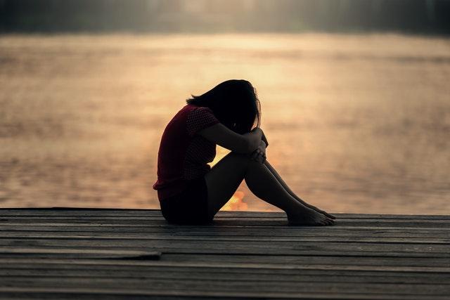 Oração Para Dominar Filho Rebelde - Menina sozinha de cabeça baixa com os braços no joelho