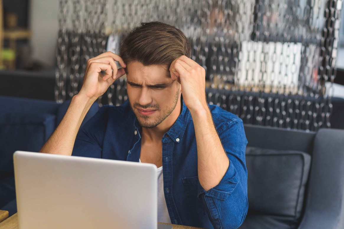 young freelancer in front of a laptop trying to think