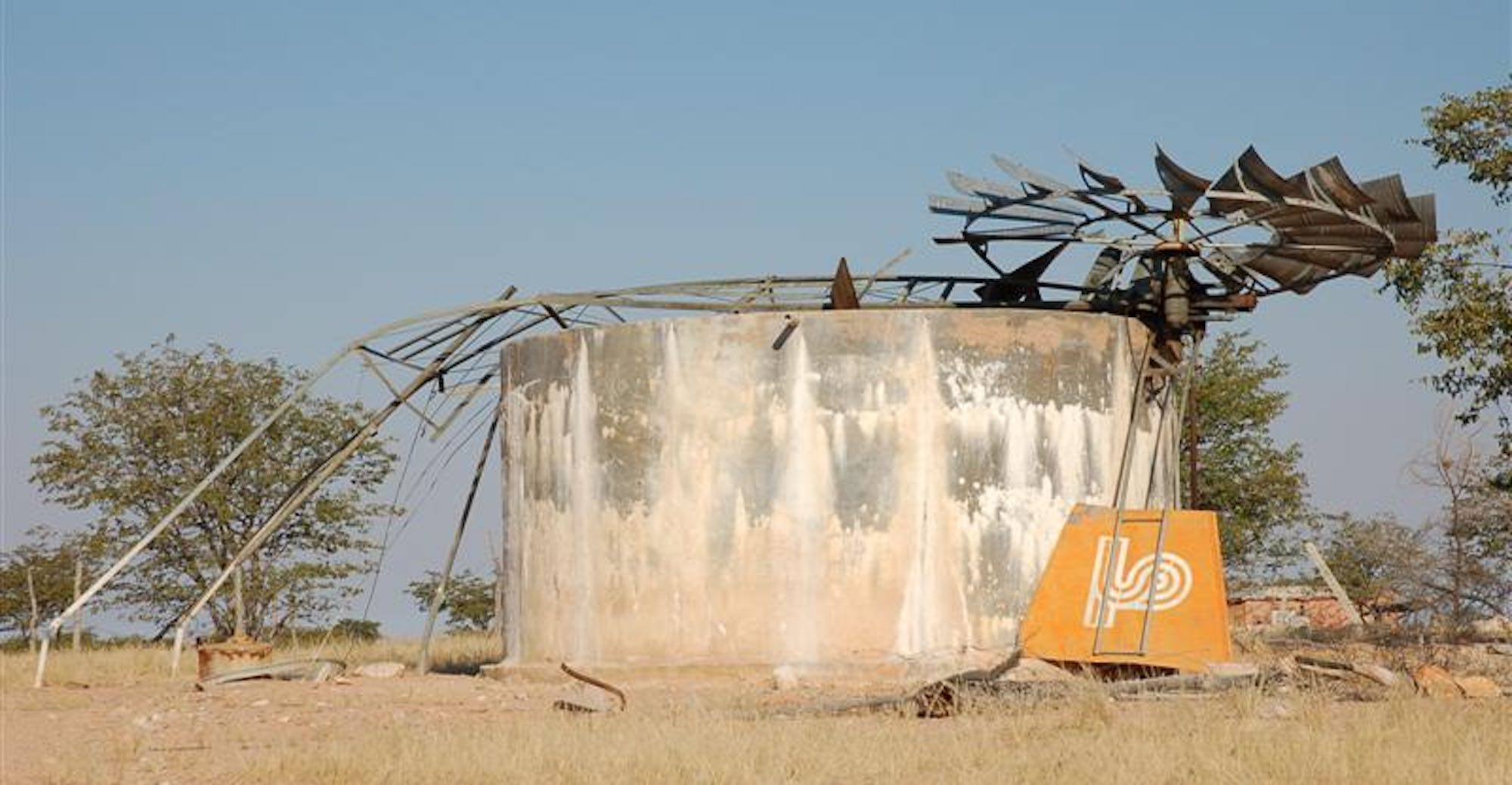 The broken remains of a windmill used to pump water from a borehole lies horizontally across a cement water tank.