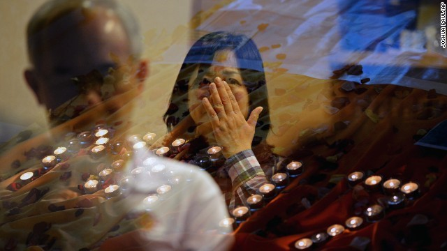 People pray for the victims of Malaysia Airlines Flight 17 at a church outside Kuala Lumpur (from CNN)